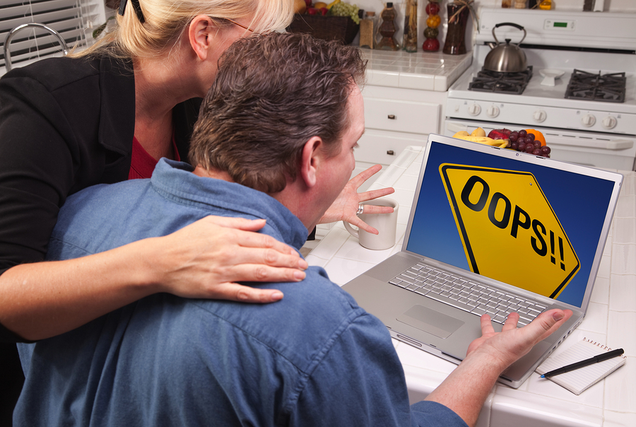 Couple In Kitchen Using Laptop with Yellow Oops Road Sign on the Screen.