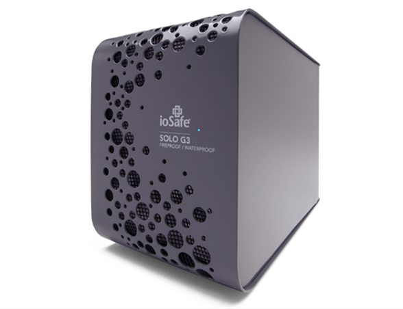 A black cube of an external hard drive with circular cut-outs is pictured.